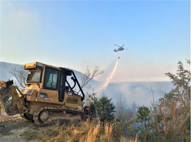 Helicopters are invaluable when assisting ground crews with line construction.  The bucket drops cool and slow fires allowing more effective use of ground crews.