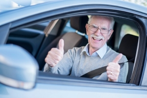 Senior man with thumbs up driving a car