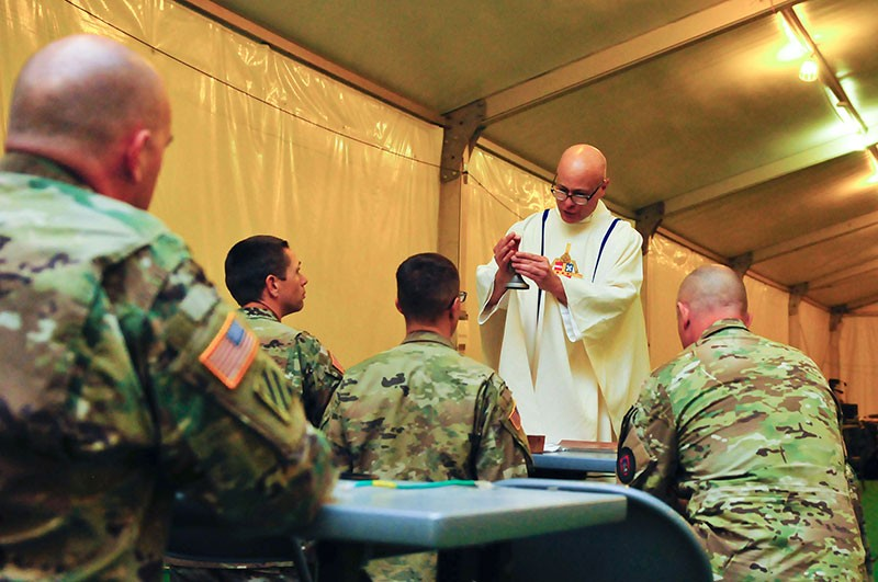 Maj. Patrick Brownell, Brigade Chaplain for the 230th Sustainment Brigade, Tennessee Army National Guard, administers a Catholic service to Soldiers training at the National Training Center, Fort Irwin, Calif. on May 6.