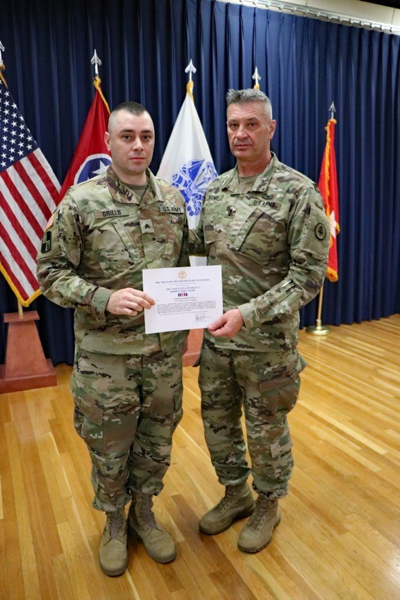 Photo of Maj. Gen. Jeff Holmes, Tennessee's Adjutant General, presents Sgt. Ryan Grillo