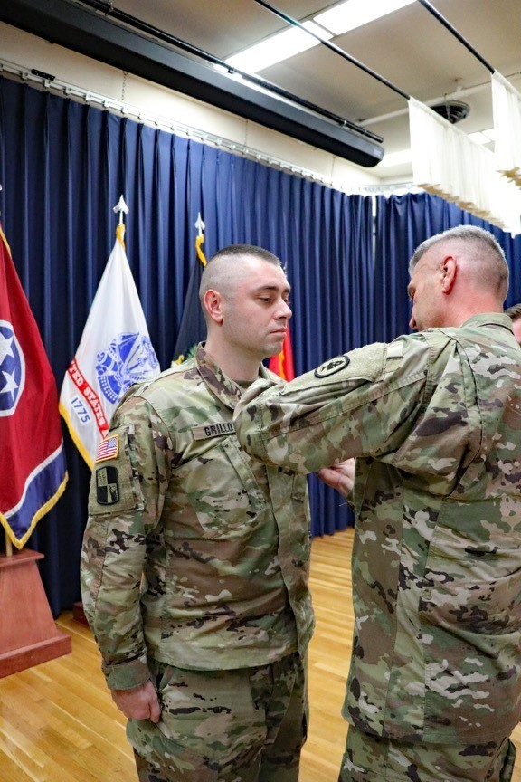 Maj. Gen. Jeff Holmes, Tennessee's Adjutant General, presents Sgt. Ryan Grillo, a Soldier with the 1176th Transportation Company, the Adjutant General's Ribbon for Valor