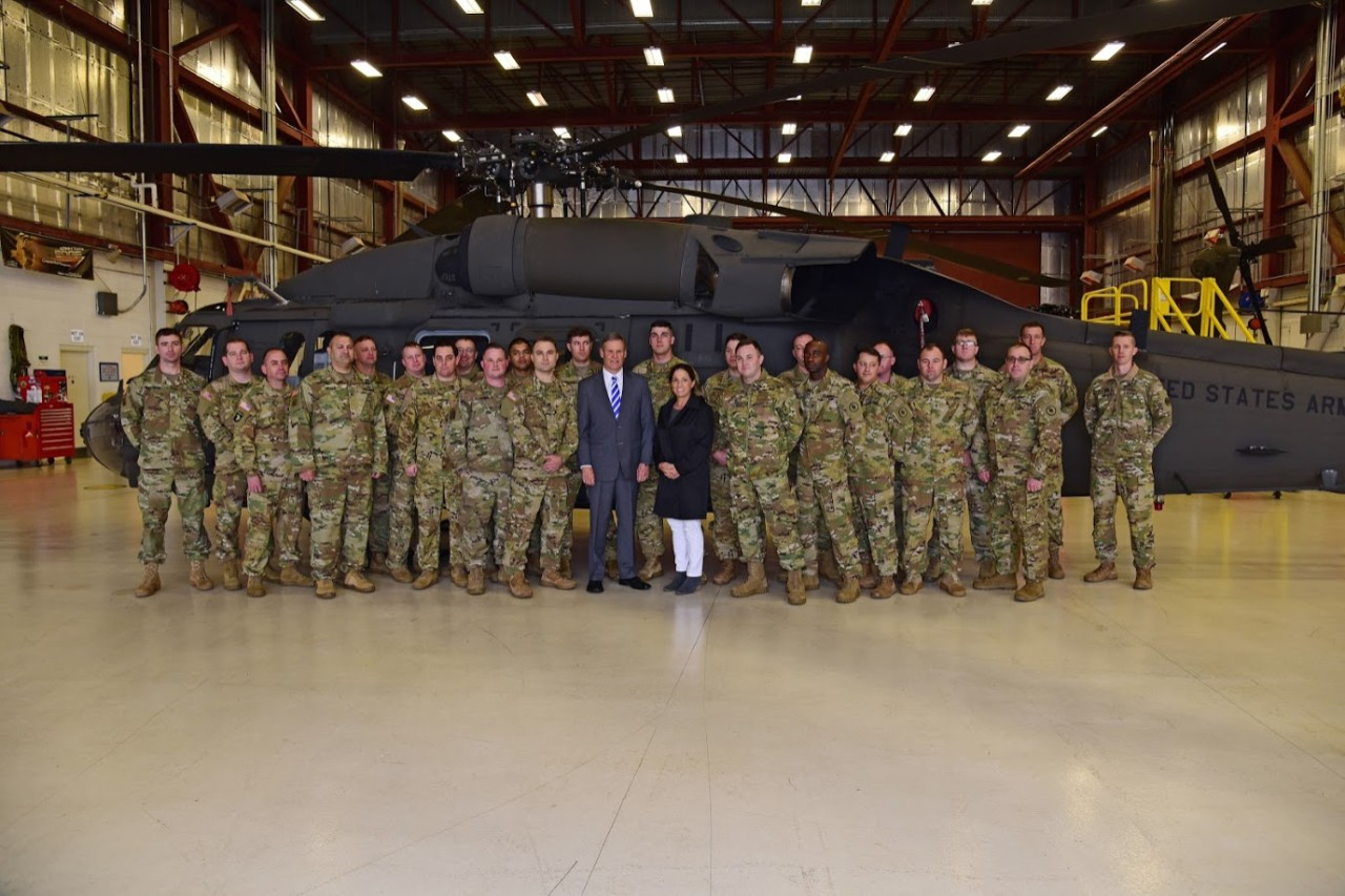 Tennessee Governor Bill Lee and First Lady Maria along with Tennessee National Guard troops in front of a helicopter