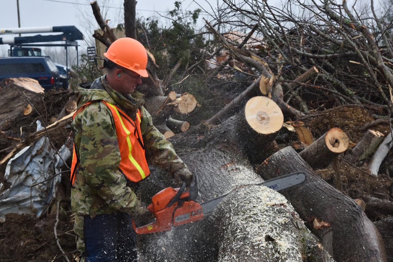 Tennessee Guard Soldier in uniform with orange construction hat using chainsaw to cut a tree into sections