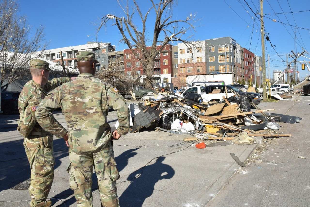 2 Tennessee National Guard Soldiers looking at rubble on the street