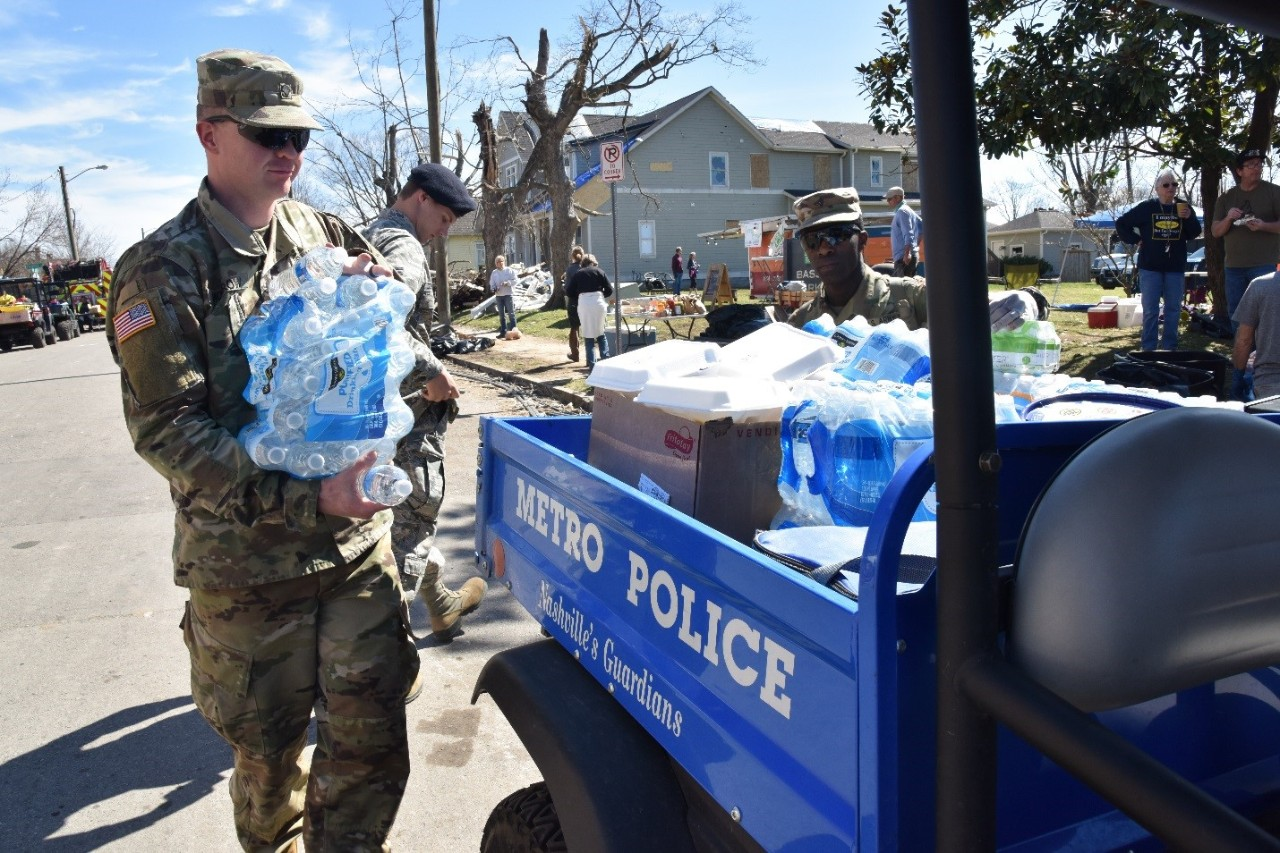Tennessee National Guard Soldiers passing out water bottles