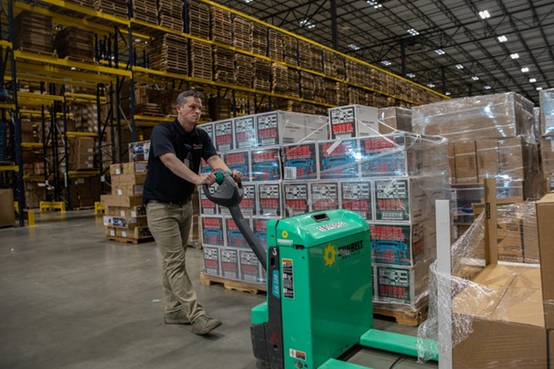 Man moving palettes of supplies in warehouse