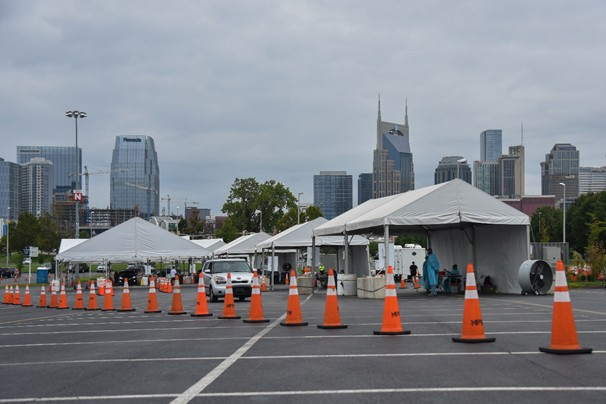 Covid-19 testing site in large parking lot with backdrop of Nashville skyline