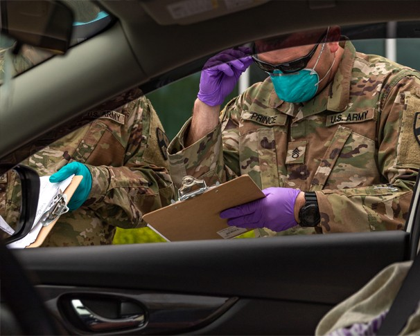 Soldier looking at clipboard beside car with someone waiting to be tested for COVID-19
