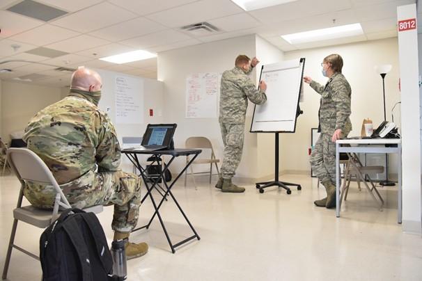 3 Military members in uniform work in an office on procedures