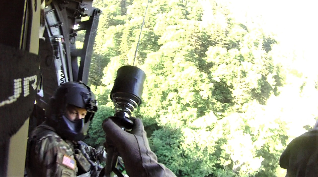 Sgt. Tim Allen begins hoist operations and lowers Sgt. 1st Class Tracy Banta, a Critical Care Flight Paramedic, to a bear attack victim in the Great Smoky Mountain National Park Area, June 18. (Courtesy photo from the Tennessee National Guard)