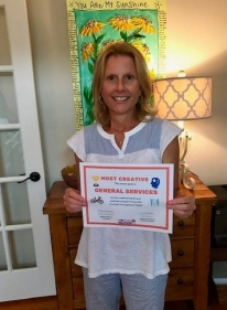 Julie holding the Most Creative Wellness Council certificate